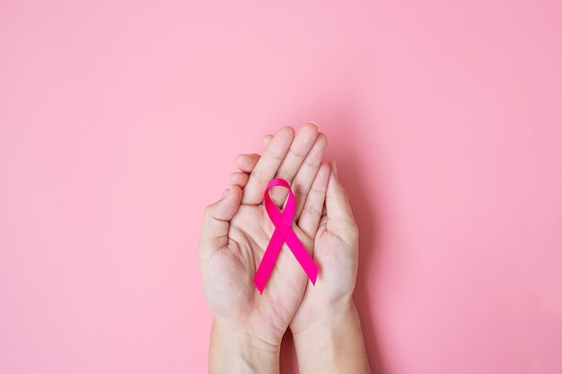 Oktober breast cancer awareness maand, volwassen vrouw hand met pink ribbon op roze achtergrond voor het ondersteunen van mensen die leven en ziekte. internationaal vrouwen-, moeder- en wereldkankerdagconcept