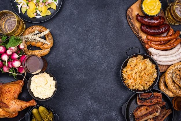 Oktoberfest gerechten: bier, krakeling, worst, gestoofde kool, aardappelsalade, halve kip en ribben op zwarte achtergrond