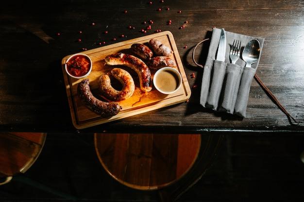 Oktoberfestvoedsel, smakelijke vleesworsten ,. een groot assortiment op een houten dienblad.