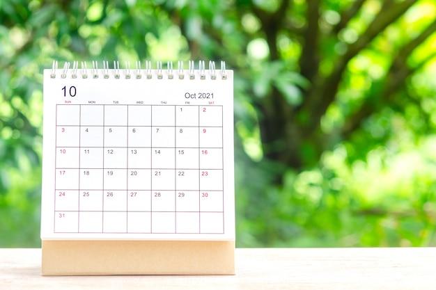 Oktobermaand, kalenderbureau 2021 voor organisator tot planning en herinnering op houten tafel met groene natuurachtergrond.