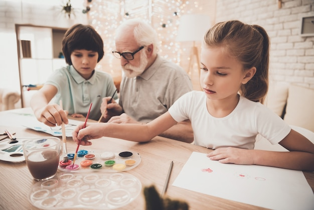 Old man paints with kids christmas with grandpa.