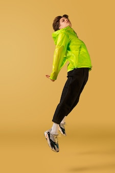 Oldschool ouderwetse jonge man dansen geïsoleerd op gele achtergrond