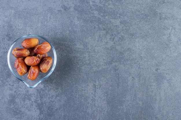 Oleaster in een glazen kom, op de marmeren achtergrond.