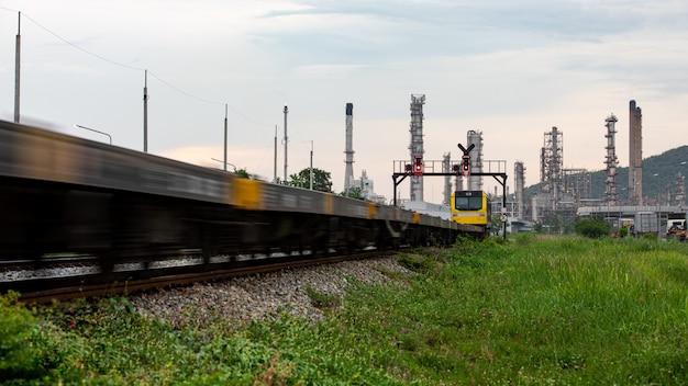 Olie en gas de opslaggebied van de raffinaderijinstallatie met trein bewegende voorgrond en avond in thailand
