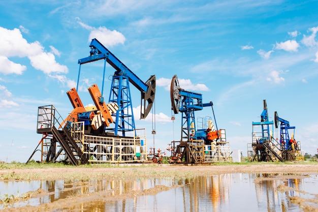 Olie en gas industrie. werkende oliepomp jack op een olieveld met reflectie op een plas. witte wolken en blauwe lucht. olie productie