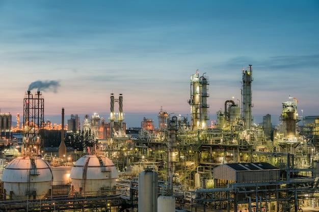 Olie- en gasraffinaderij of petrochemische industrie op zonsondergang achtergrond, gasopslag boltank en destillatietoren in industriële petroleum