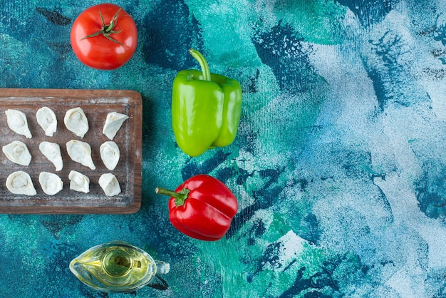 Olie en groenten naast turkse ravioli op een bord, op de blauwe tafel.