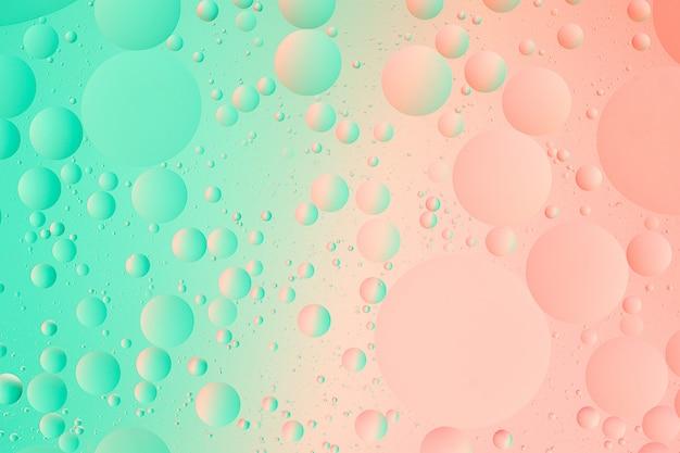 Olie op water macrofotografie van abstracte groene en roze kleurverloop achtergrond