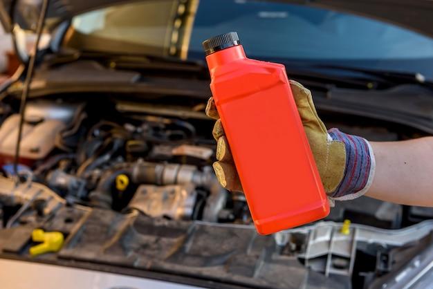 Olie verversen concept. mannenhand in handschoen met oliefles en automotor close-up