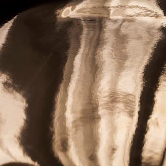 Olieachtige gouden textuurachtergrond met schaduwen