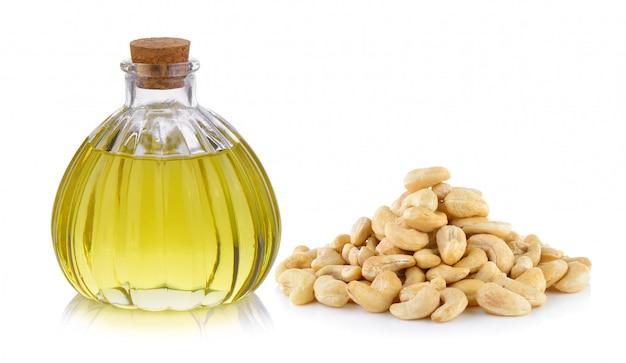 Oliefles en cashewnoot op witte ruimte