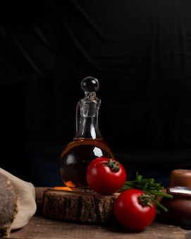 Oliefles, tomaten en kruiden op het stuk hout