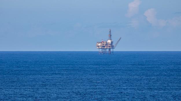 Olieplatform midden van de zee op een zonnige dag.
