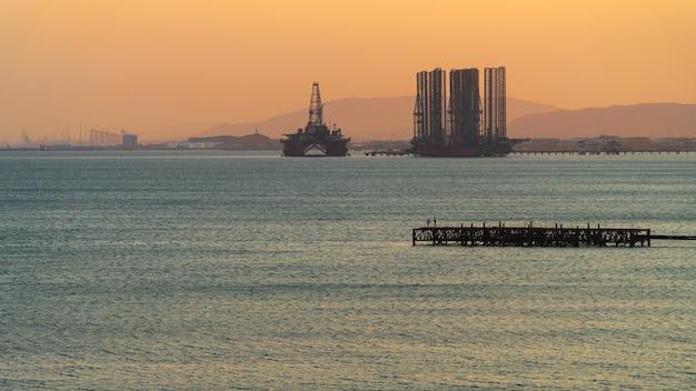 Olieplatforms in de zee bij zonsondergang