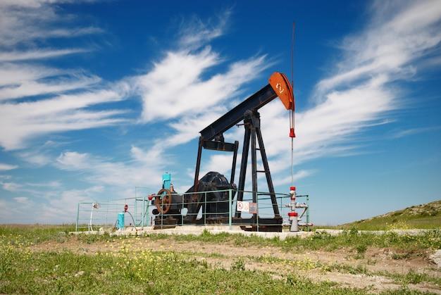 Oliepomp. olie-industrie apparatuur in groene weide