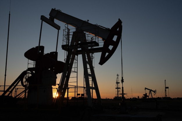 Oliepomp op oranje zonsondergang