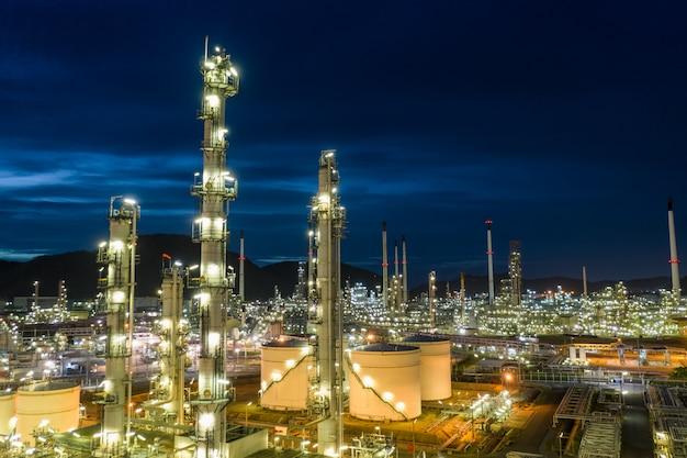 Olieraffinaderij en gas petrochemische industrie met opslagtanks stalen pijpleiding gebied bij schemering luchtfoto van drone