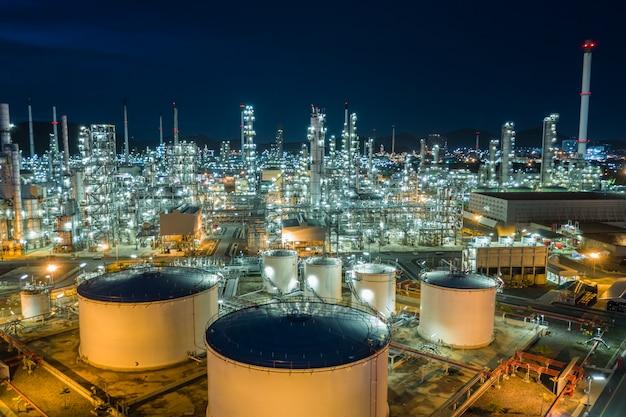 Olieraffinaderij en gas petrochemische industrie met opslagtanks stalen pijpleiding gebied bij schemering luchtfoto