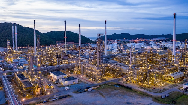 Olieraffinaderij en gas petrochemische industrie met opslagtanks stalen pijpleiding gebied bij schemering
