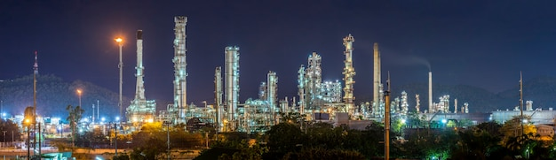 Olieraffinaderij met waterdamp in hamburg, duitsland, petrochemische industrie 's nachts.