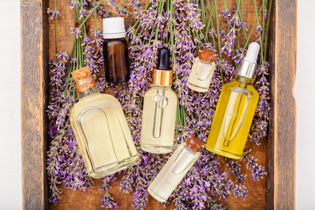 Olieserumoliën op lavendelbloemen in bruine houten kist. essentiële olie van lavendel, serum, body butter, massageolie, vloeistof. plat leggen. huidverzorging lavendel cosmeticaproducten. stel natuurlijke spa-schoonheidsproducten in.