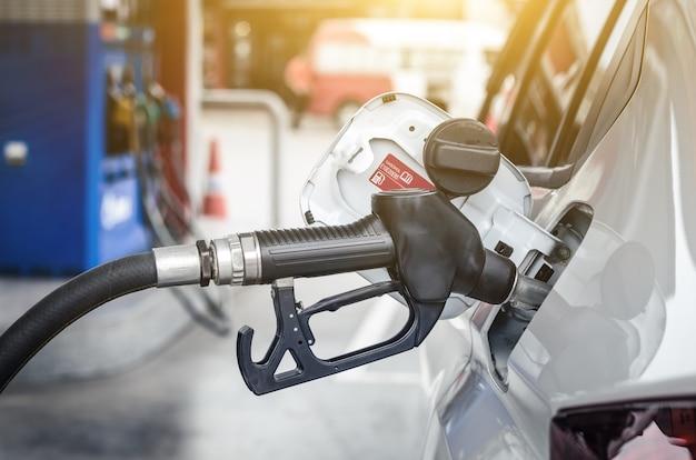 Oliestation en brandstofmondstuk in auto, autobrandstofconcept
