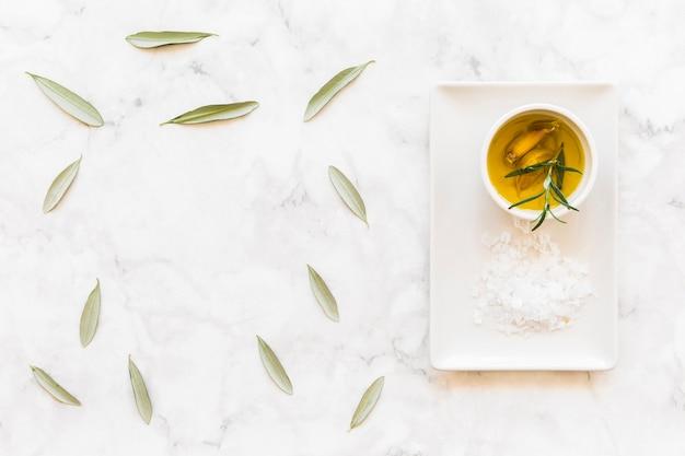 Olijfblaadjes met knoflookteen en rozemarijn kruidenolie en lat op de schaal