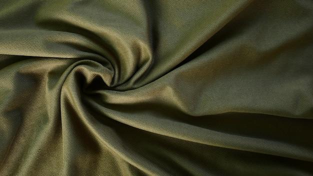 Olijfgroen zijde satijn textuur, groene katoenen stoffen achtergrond, zijde beddengoed textuur