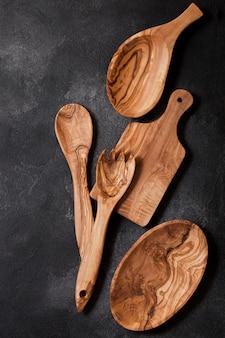 Olijfhout keukengerei met snijplank en kom op stenen tafel. bovenaanzicht.