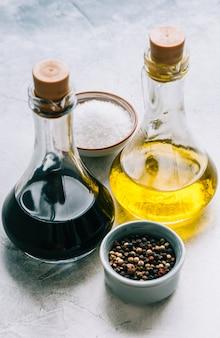 Olijfolie en balsamico azijn in flessen op tafel met kruiden. salade saus
