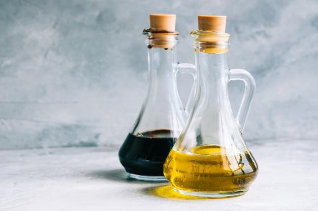 Olijfolie en balsamico azijn in flessen op tafel. salade saus