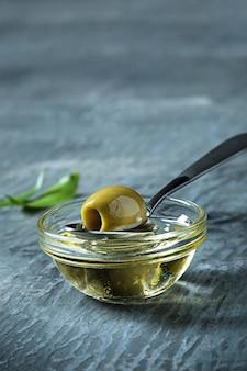 Olijfolie en olijftak op houten lijst
