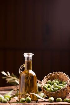 Olijfolie en olijven op houten rustieke tafel