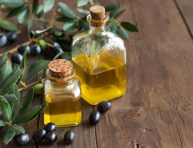 Olijfolie en verse olijven op houten tafel close-up met kopie ruimte