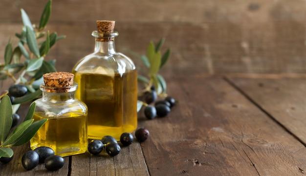 Olijfolie en verse olijven op houten tafel