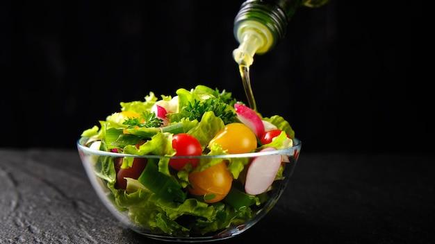 Olijfolie gieten van fles op groentesalade, gezonde en dieetvoeding van verse ingrediënten in glazen kom op zwarte achtergrond