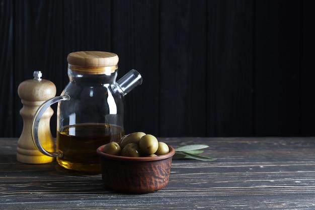 Olijfolie, groene olijven en kruiden op een houten tafel met ruimte voor tekst.