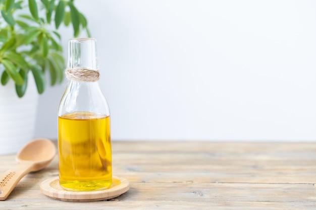 Olijfolie in een fles, een lepel en een bloem in een pot op een houten tafel op een witte achtergrond. ruimte kopiëren.
