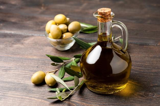 Olijfolie in een fles en groene olijven