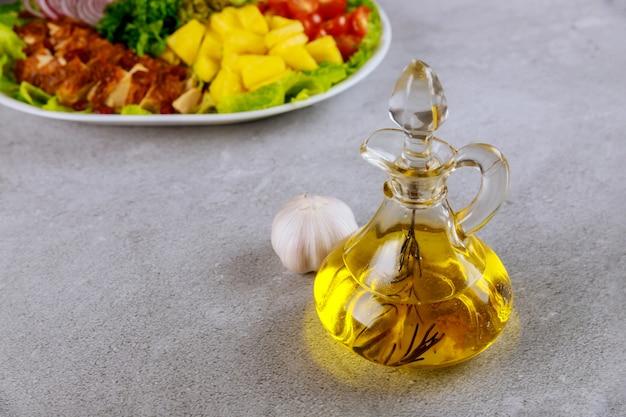 Olijfolie in glazen fles met kleurrijke salade