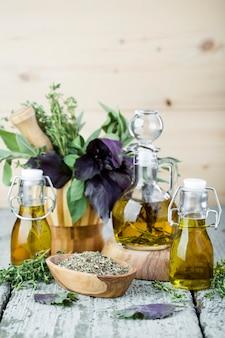 Olijfolie met kruiden en specerijen op houten achtergrond