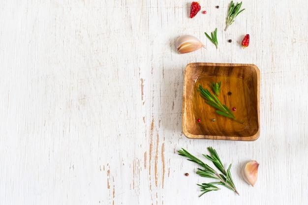 Olijfolie met rozemarijn in een houten kom en kruiden. bovenaanzicht met kopieerruimte