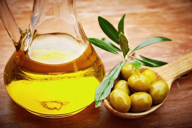 Olijfolie met verse olijven op rustiek hout