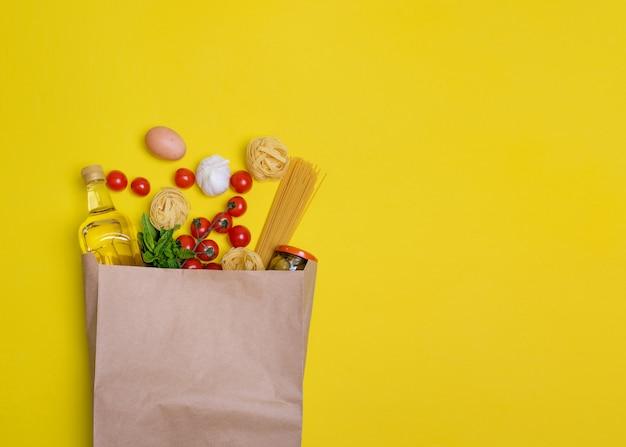 Olijfolie, pasta, tagliatelle, olijven, ei, cherrytomaatjes, knoflook in een papieren zak op geel