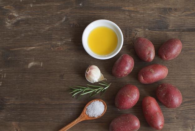 Olijfolie porseleinen bord rozemarijntak pepermix knoflook kruiden kruiden rauwe aardappel