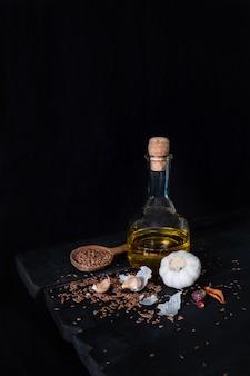 Olijfoliefles, knoflook en zaden in een donkere, rustieke ondergrond. artistieke foto van olie en kruiden op oude zwarte tafel geschoten in rustige ciaroscurro stijl