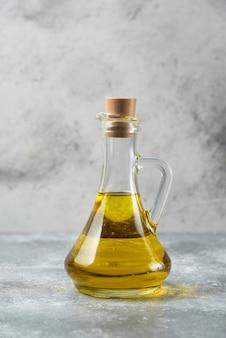 Olijfoliefles op marmeren tafel.