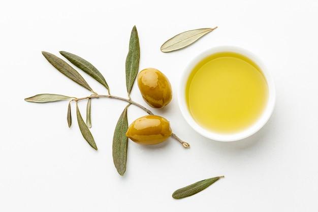 Olijfolieschotel met bladeren en gele olijven