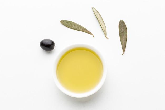Olijfolieschotel met bladeren en zwarte olijf