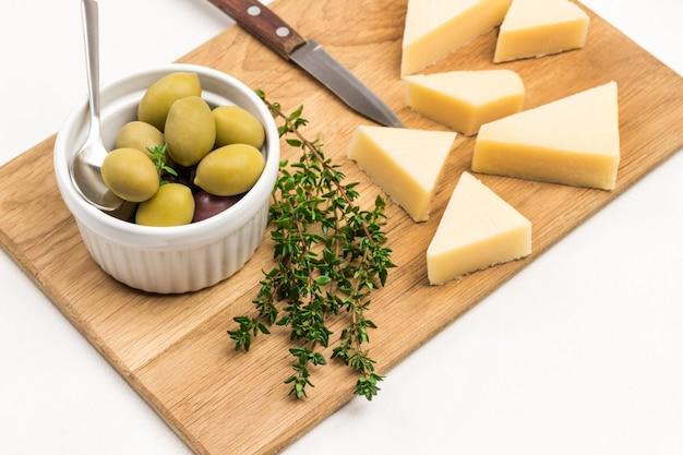 Olijven in ceramische kom. parmezaanse kaas en takjes tijm op snijplank. bovenaanzicht.
